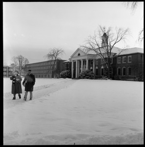 Students walking out of Goodell Library on a snowy day, with Bartlett Hall in the background