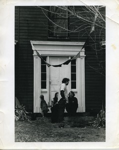 Cathy Rogers, Ira Krasnik, and Michael Curry seated with a dog by the front door, Montague Farm Commune