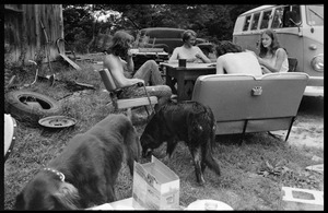 Commune members seated at a card table in front of Montague Farm Commune, dogs in the foreground and Volkswagen microbus behind (Susan Mareneck, far right)