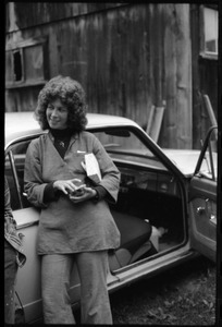 Unidentified woman standing by a car with open door in front of the barn, Montague Farm commune