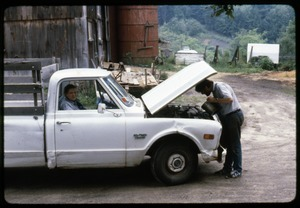 Tony Mathews looking under the hood of pickup truck by the barn, his mother in the passender seat, Montague Farm Commune