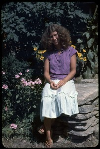 Amy Wainer seated on a stone wall, Montague Farm Commune