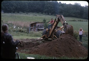 Backhoe digging the foundation for the greenhouse as Peter Natti and Janice Frey look on, Montague Farm Commune