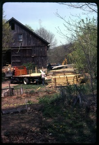 Lumber being stacked in front of the barn, Montague Farm Commune