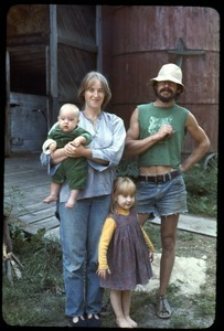 Sandra Marr, Smokey Fuller, and children in front of the barn, Montague Farm Commune