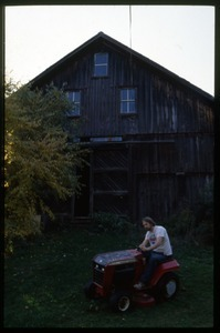Peter Natti riding a lawnmower in front of the barn, Montague Farm Commune