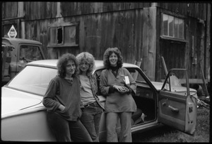 Janice Frey (center) and two friends standing by a car with open door in front of the barn, Montague Farm commune
