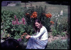 Anna seated with a dog in front of lupines, lilies, and other flowers; Montague Farm Commune
