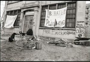 """Women's occupation of the Architectural Technology Workshop, Harvard University: two dogs, occupier, and bicycles outside ATW, graffiti and signs announcing """"Liberated building"""" and """"Women, this building is ours"""""""