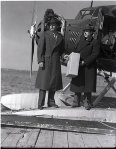 """Bill Wincapaw (son) handing a package to William H. Wincapaw (the """"Flying Santa Claus"""") next to their floatplane"""