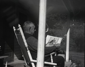 Older man on a porch in a rocking chair, looking at Norman Rockwell's illustration of Thanksgiving dinner
