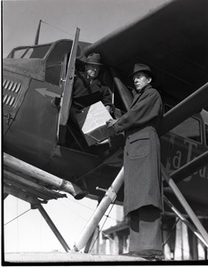 """Bill Wincapaw (son) handing a package to William H. Wincapaw (the """"Flying Santa Claus"""") in their floatplane"""