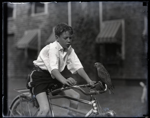 Charles Sanborn on bicycle with parrot