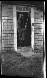 Reuben Austin Snow, the cross-dressing hermit of Cape Cod, in doorway to house