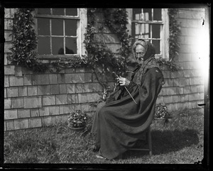 Reuben Austin Snow, the cross-dressing hermit of Cape Cod, seated in front of cottage, knitting