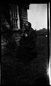 Reuben Austin Snow, the cross-dressing hermit of Cape Cod, knitting in front of house