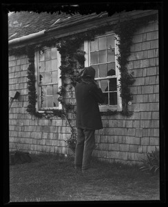 Reuben Austin Snow, the cross-dressing hermit of Cape Cod, looking in the cottage window