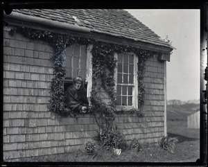 Reuben Austin Snow, the cross-dressing hermit of Cape Cod, leaning out a cottage window