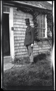 Reuben Austin Snow, the cross-dressing hermit of Cape Cod, wearing a top hat outside the cottage