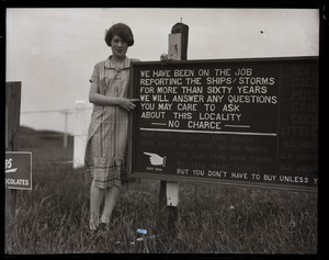 Woman (possibly granddaughter of Isaac Morton Small) posed with sign near Highland Lighthouse