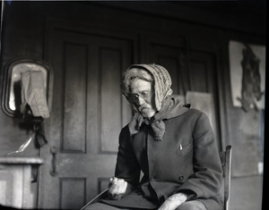 Reuben Austin Snow, the cross-dressing hermit of Cape Cod, stoking a fire in a wood stove