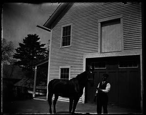 Groomsman and horse in front of a barn