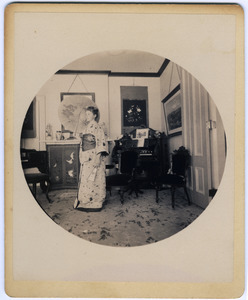 Abby F. Blanchard in the parlor, with parasol and kimono