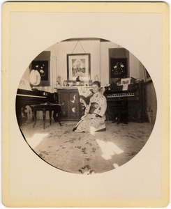 Abby F. Blanchard kneeling in the parlor, with fan and kimono
