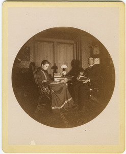 Abby F. Blanchard and C. P. Blanchard, reading at a table in the parlor