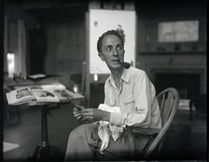 Norman Rockwell seated in a Windsor chair in his studio, holding a paintbrush