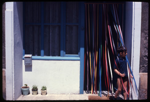 Boy walking through a doorway decked with colored streamers