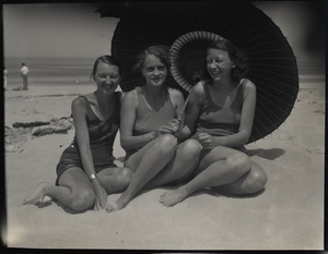 Isabelle Moulton, Mrs. Stewart Sanborn (Miriam?), and Mrs. Riker in bathing suits at the beach, seated under a parasol