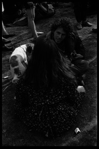 Crowd on Cambridge Common: couple seated on the grass, with puppy