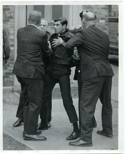 Fr. Nicholas Riddle being forced from St. John's Cathedral after he attempted to read a statement against the war in Vietnam at the church. He and 7 others were arrested and charged with disorderly conduct, posting bail of $250 each