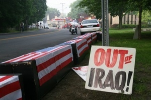 Fake caskets draped in American flags lining the road, with sign reading 'Out of Iraq'