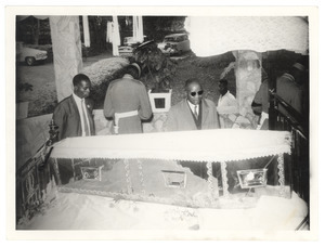 Unidentified man pays his final respects over the casket of W. E. B. Du Bois