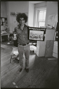 Abbie Hoffman holding copies of Steal This Book and The World of Currier and Ives