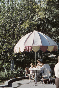 Family lunches at table under umbrella