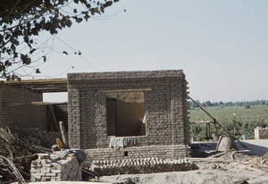 Building an adobe house on farmland