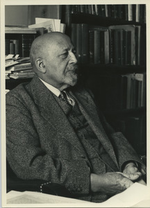 W. E. B. Du Bois sitting in his library