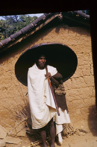 Munda man carrying an umbrella woven from cane or bamboo
