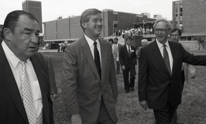 Ceremonial groundbreaking for the Conte Center: unidentified man, Gov. William Weld, and Provost Richard O'Brien walking to the site of groundbreaking