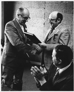 James Richard Beattie receiving book from Merle Howes, while Chancellor Randolph W. Bromery applauds