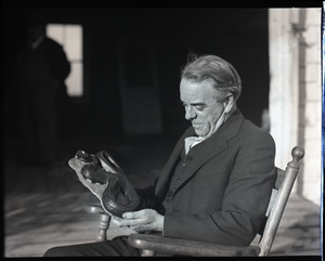 William F. Clapp, seated, examining a model of a snake