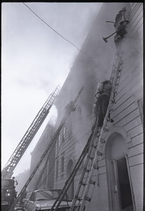 Firefighters climbing ladders to burning building in Dorchester