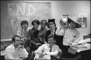 At the Boston University News Office: staff of BU News, Don McClean holding sign, Peter Simon top left, unidentified woman, unidentified man, Clif Garboden, Ed Siegel, and Joe Pilati in front with typewriter