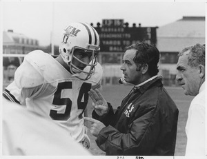Bob Pickett and Dick MacPherson talking with unidentified football player