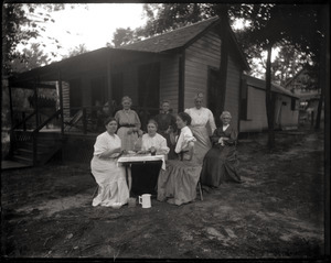 Nurses seated at a table in front of a cottage