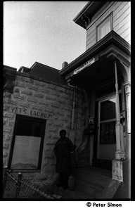 African American woman with broom standing on the front steps of 199 Harvard St., Cambridge, Mass.; Vet's Laundry sign in background and banner over doorway reads 'Cambridge is a city, not a highway'