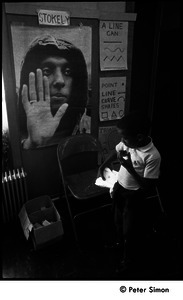 African American boy in front of a poster of Stokely Carmichael, the Liberation School